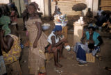 Accra, market street scene with woman breastfeeding child