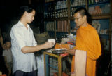 Bangkok, Buddhist monk receiving food from shop