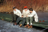 New York, Manhattan, three ice skaters sitting on side of pond