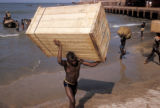 Accra, longshoremen carrying cargo from surfboats