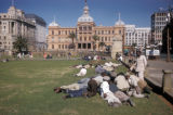 Pretoria, Church Square, men lounging on lawn with Raadsaal in background
