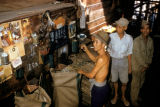 Bangkok, men filling sacks in rice mill