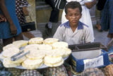 Cartagena, boy with display of sliced pineapple in street market