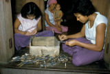 Thailand, workers polishing bronze tableware