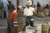Chichicastenango, men weighing dried goods at outdoor market