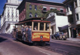 San Francisco, men riding cable car on Nob Hill