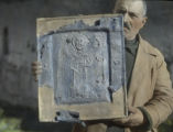 Svanetina man holding 12th century religious icon from Church of Virgin above Ushgul