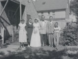 Bride and groom posing with their family in backyard