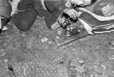 Man laying on ground lighting opium pipe