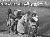 Tibetan women fetching water from river in Tibetan Plateau
