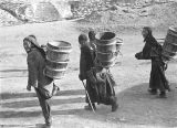 Tibetan women carrying water in Tibetan Plateau