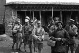 Chinese soldiers with bayonets in front of prayer wheels in Tibetan Plateau