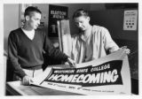 Two students displaying Homecoming banner