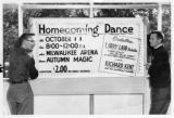 Two students displaying banner for Homecoming dance