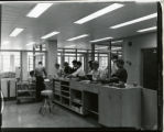 Students at service desk in Mellencamp Hall Library