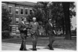 Chancellor J. Martin Klotsche walking outside with two unidentified men
