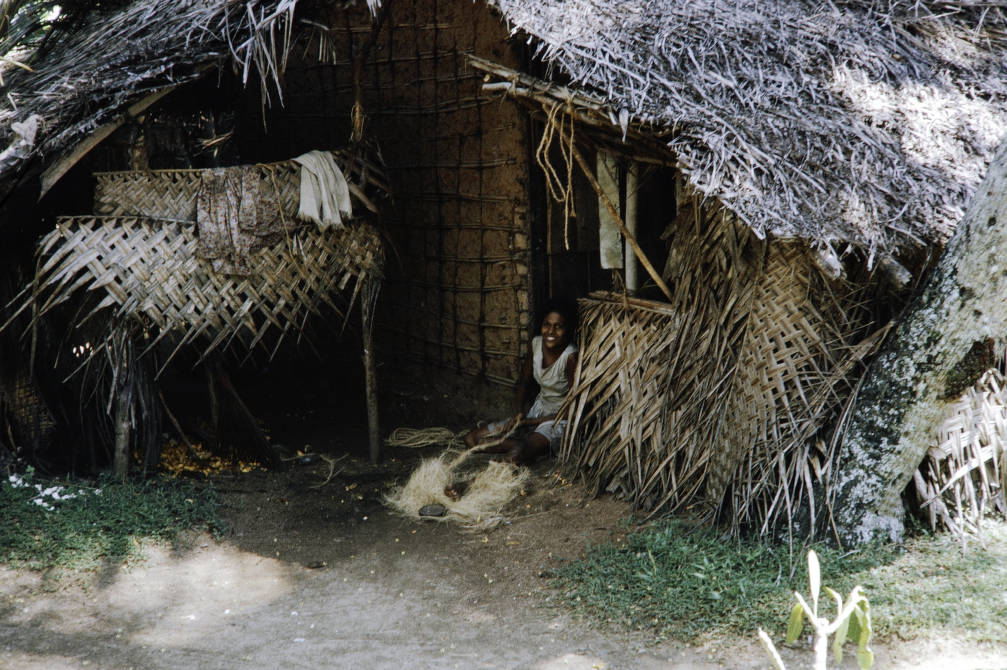 Sri Lanka, woman weaving fibers in doorway of thatched